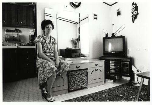 [A woman in a floral dress sits on a dressing table in a living room ]