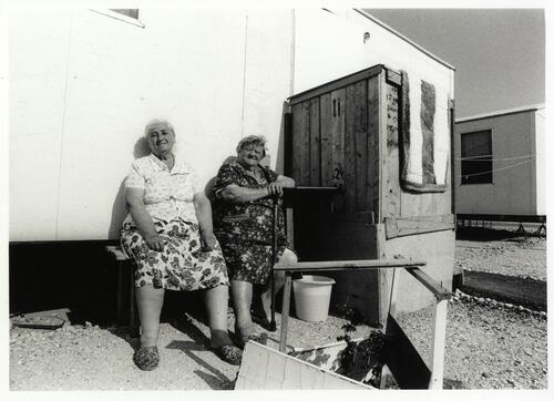 [Two women, one of them with a walking stick, sit outside a prefabricated house]