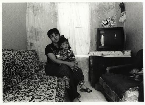 [A woman sits with a child on a couch covered with a decorated rug, with a television set in the background]