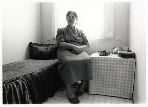 [A woman sits next to a bed and a small table holding a tin and a portrait]