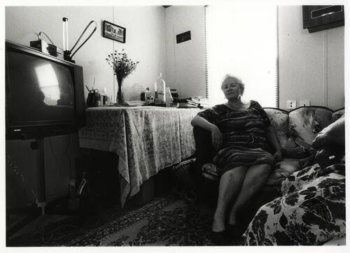 [A woman sits on a couch with a table holding books in the background and a Television in the foreground]