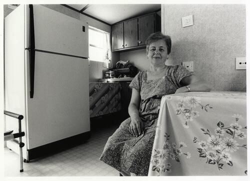 [A woman in a floral dress sits next to a table with the kitchen in the background]