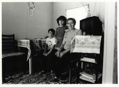 [A woman sits with two children in front of a Television and a dining table]