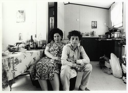 [A woman in a floral dress and a boy sit next to a kitchen area]