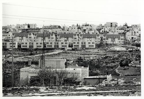[View of a neighbourhood with housing in the background and a construction site]