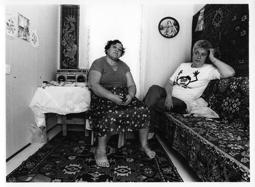 [Two women sit in a room partially covered in rugs with a table and a radio in the background]