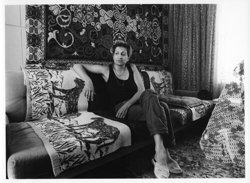 [A woman sits on a couch in a room decorated with rugs]