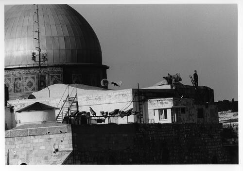 [A person stands on a rooftop next to the dome of a religious building]