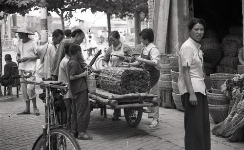 [A bail of straw wrapped in bamboo in handled by a woman with piles of weaved baskets on her back]