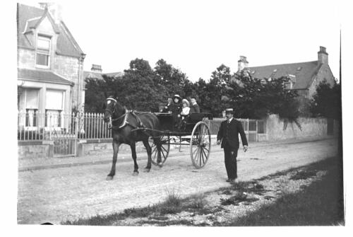 Ida and Fred [Miller] in George Squair's dogcart outside Loch Maree House, Nairn.