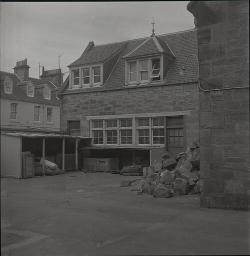 View of building exterior with outdoor shelters and a pile of stone blocks