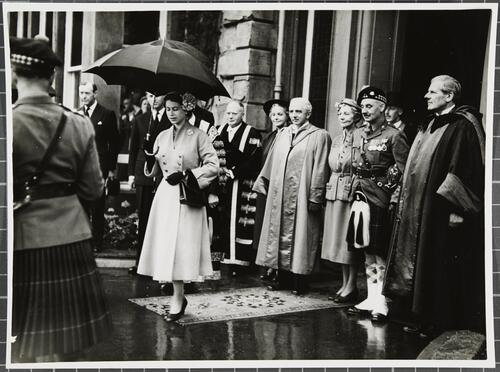 Queen Elizabeth II holds an umbrella