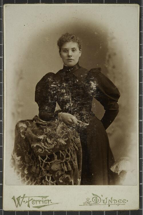 Studio portrait of a woman leaning against a stool.