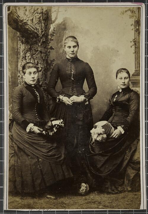 Group studio portrait of three women, two of which are seated and one standing.