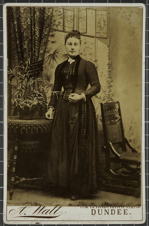 Studio portrait of a woman standing next to a table with a flower.