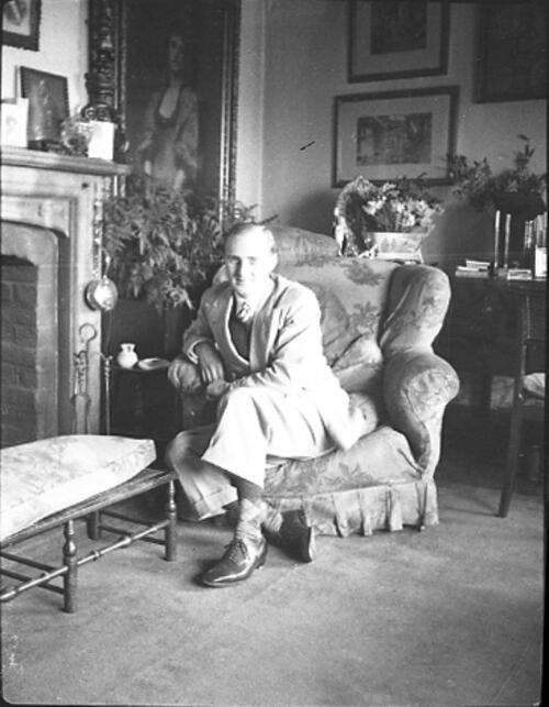 [Man sitting on a armchair by a fireplace]