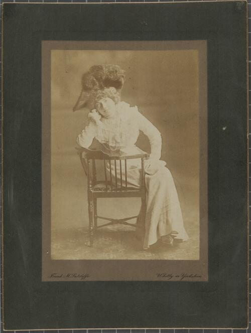 [Woman sitting leaning against an armchair]