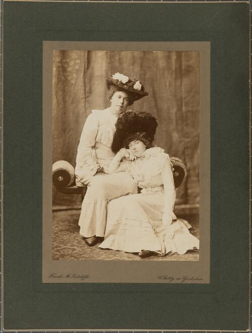 [Portrait of two women, one sitting on the floor, leaning against the other]