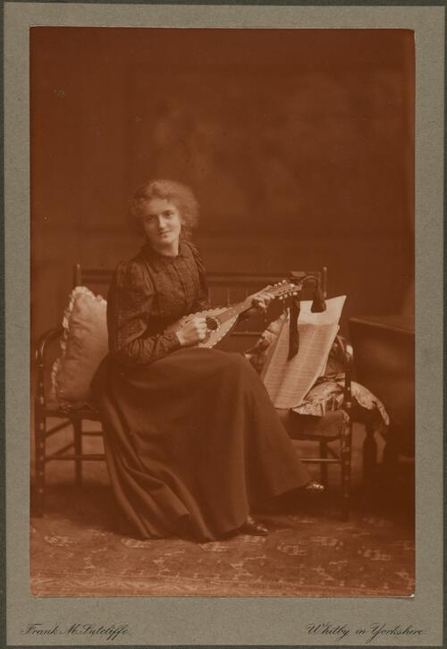 [Woman sitting holding an instrument]