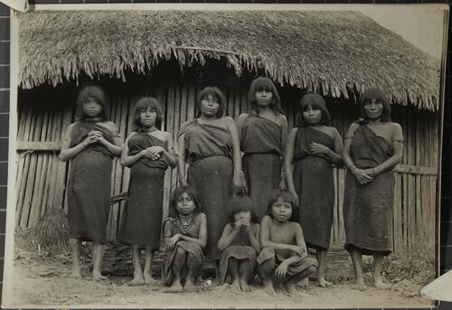 [A group of women and girls stand outside a hut]