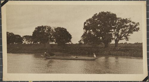 [Two men rowing in a long canoe with a sail]