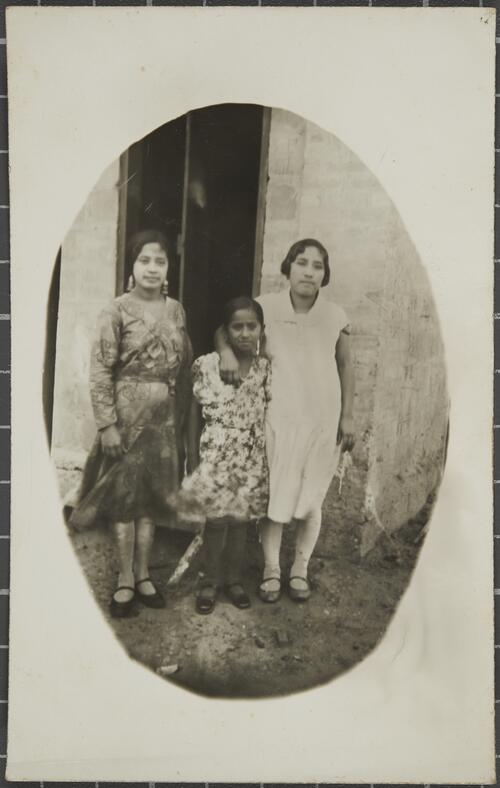 [Three girls stand next to a door]