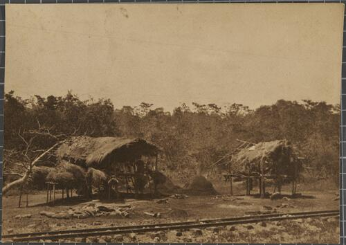 [Two wooden huts with raised platforms next to a railway]
