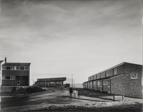 [East Kilbride - Westwood IX, a woman walks with two children close to two storey houses]