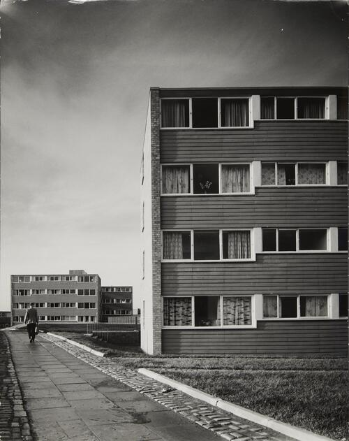[East Kilbride - Westwood IX, a man walks between two apartment blocks]