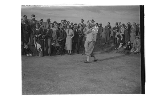 Hector Thomson or J McLean driving on the 13th hole (Croupie) of the Golf House Club course, Elie. Mrs Holm and crowd watching.