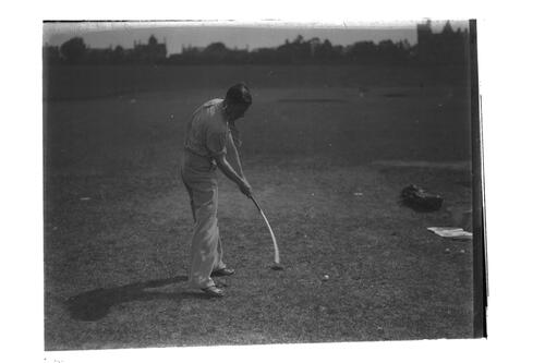 A golfer practising his swing on the Old Course, St Andrews.