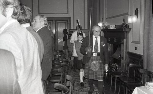 Walter Maronski (President) parades with sword before piper and cook with haggis, the 100th Celebration of the St Andrews Burns Club, at McArthur's Cafe.