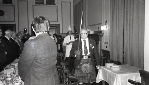 Walter Maronski (President) parades with sword before piper and cook, the 100th Celebration of the St Andrews Burns Club, at McArthur's Cafe.