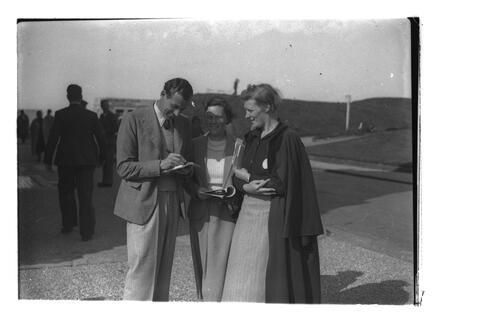 Golfer (?Hector Thomson) signing autographs outside the R&A on Golf Place, St Andrews