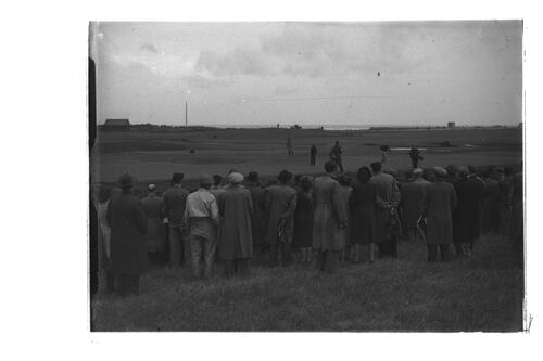 N Von Nida putts watched by fellow players, caddies and crowd, [?the 15th green] the Old Course, St Andrews.