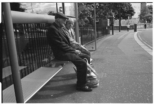 [Elderly Couple at Bus Stop]