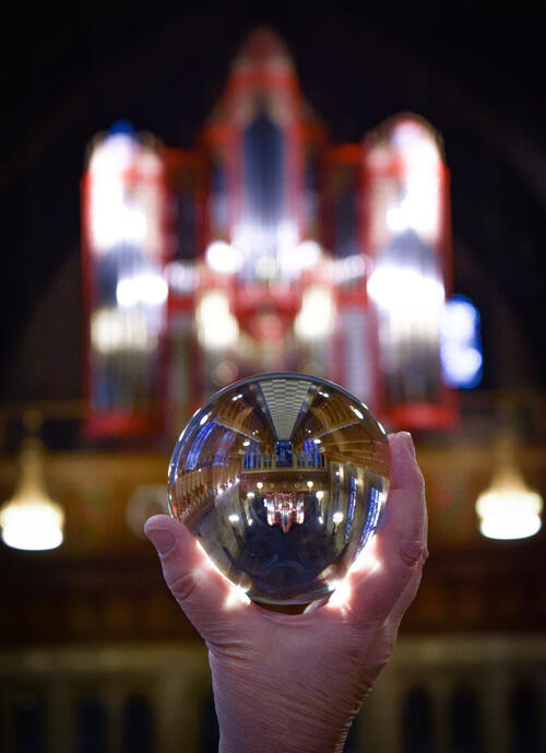 Lensball held with organ in background, St Salvator's Chapel, University of St Andrews