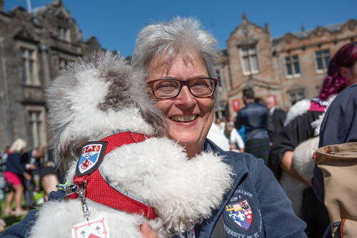 Member of staff at the University of St Andrews with therapet on Graduation Day