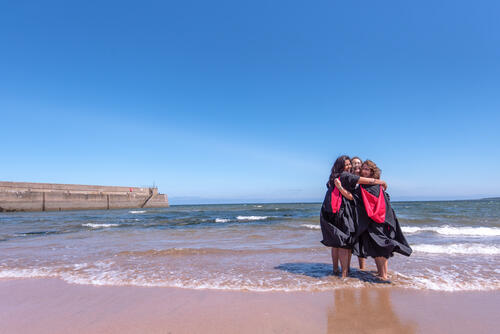 Graduates of the University of St Andrews hugging on the East Sands after Graduation