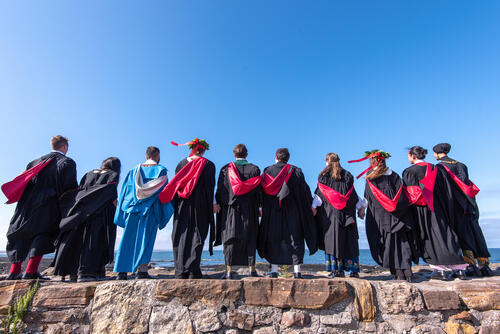 A group of graduates from the University of St Andrews in national dress on the Pier following Graduation