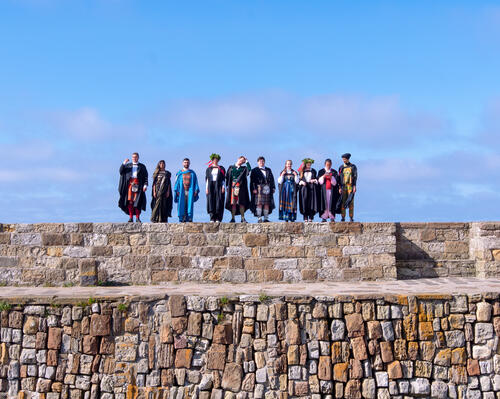 A group of graduates from the University of St Andrews in national dress doing a Pier Walk following Graduation