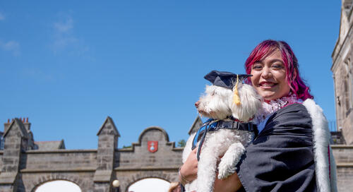 Graduate in traditional dress from Hawaii with emotional support dog at the University of St Andrews