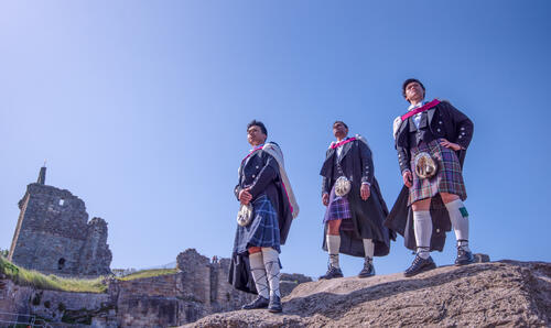 Three graduates from the University of St Andrews on Castle Sands