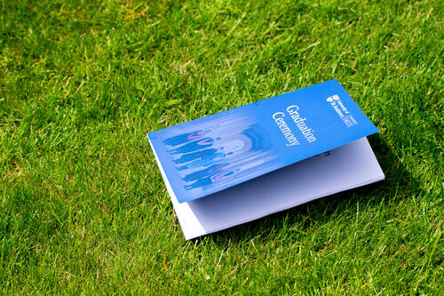 Graduation Booklet from the University of St Andrews on the grass