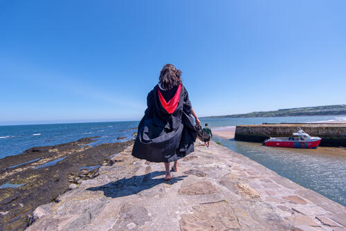 Fresh Graduate from the University of St Andrews walking on St Andrews Pier