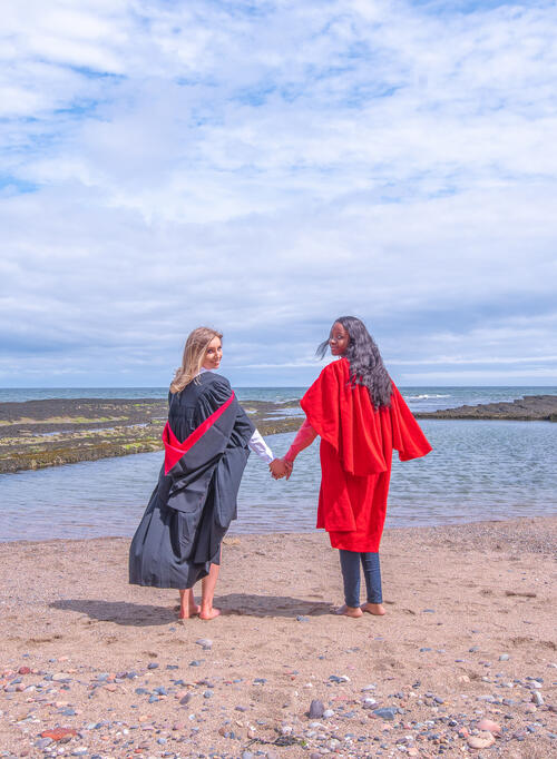 Graduate and Undergraduate from the University of St Andrews holding hands on Castle Sands on Graduation Day