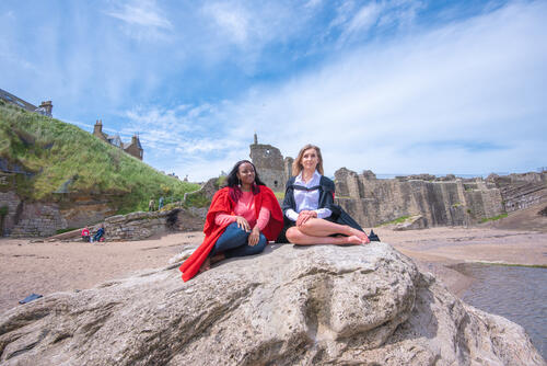Graduate and Undergraduate from the University of St Andrews on the rocks at Castle Sands on Graduation Day