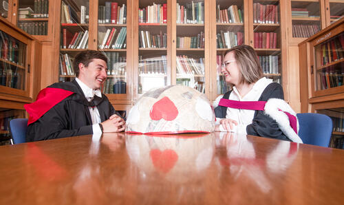 Graduate couple from the University of St Andrews posing with heart sculpture in the School of Classics library