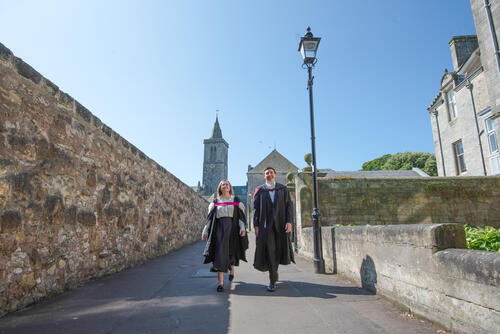 Graduate couple from the University of St Andrews walking down the street after Graduating