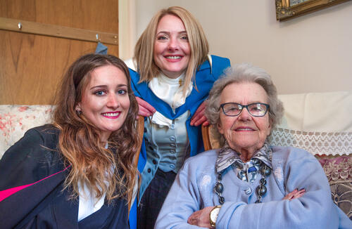 Psychology graduate and her teacher from the University of St Andrews visiting a local friend on her Graduation Day